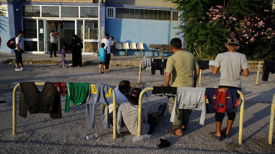 In this photo taken on Tuesday, June 16, 2015 migrants gather outside an old indoor swimming pool in Mytilene, on the northeastern Greek island of Lesbos. Lesbos, Greece's third-largest island, is bearing the brunt of the migrant crisis. More than 25,000 people have arrived on the island of about 80,000 inhabitants since the start of the year - nearly half of the 55,000 who have reached Greece by sea from Turkey. (AP Photo/Thanassis Stavrakis)