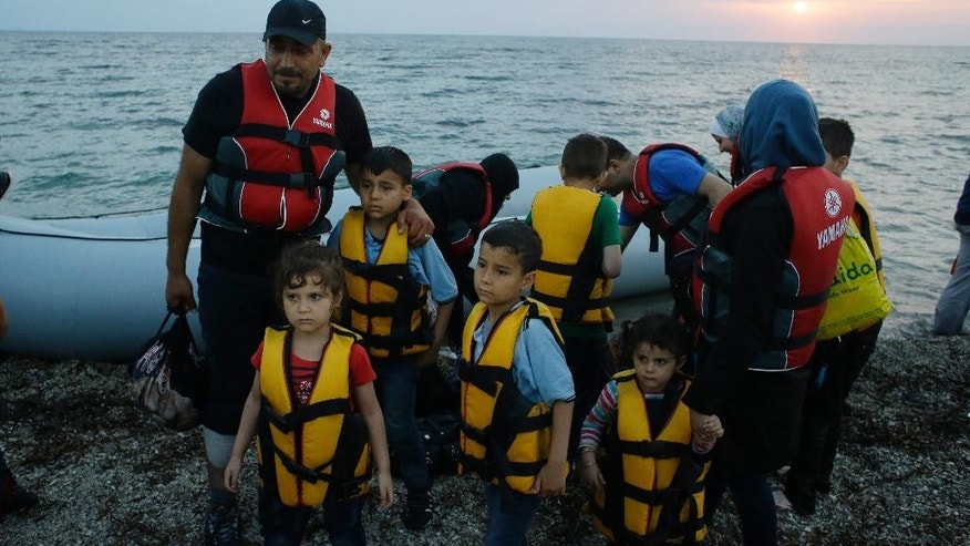 In this photo taken on Thursday, June 18, 2015, Syrians migrants arrive by dinghy from the Turkish coasts, at a Mytilene's beach, on the northeastern Greek island of Lesbos. Lesbos, Greece's third-largest island, is bearing the brunt of the migrant crisis. More than 25,000 people have arrived on the island of about 80,000 inhabitants since the start of the year - nearly half of the 55,000 who have reached Greece by sea from Turkey. (AP Photo/Thanassis Stavrakis)