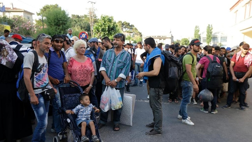 In this photo taken on Monday, June 15, 2015, Syrians migrants gather during a protest, demanding better living conditions and faster processing of their asylum registrations, at the port of Mytilene, on the northeastern Greek island of Lesbos. Lesbos, Greece's third-largest island, is bearing the brunt of the migrant crisis. More than 25,000 people have arrived on the island of about 80,000 inhabitants since the start of the year - nearly half of the 55,000 who have reached Greece by sea from Turkey. (AP Photo/Thanassis Stavrakis)