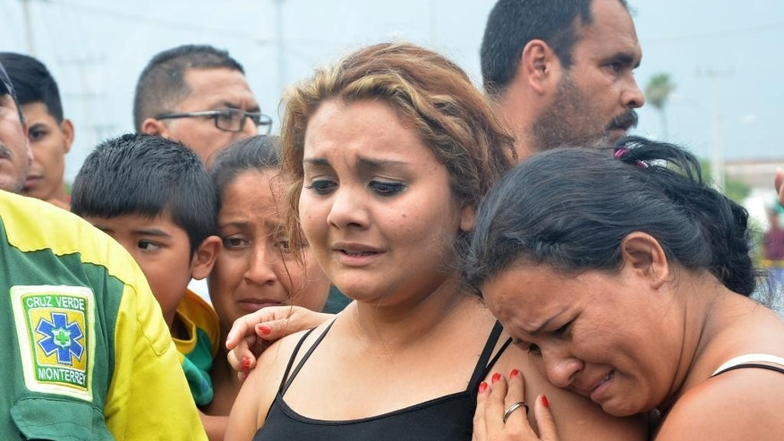 Relatives wanting information about their loved ones gather outside a beer distribution center after it was attacked in the town of Garcia, on the outskirts of the northern city of Monterrey, Mexico, Friday, June 19, 2015. A state government official said that the attackers invaded the property, demanded money from the workers and then started shooting, killing at least 10 people. The victims were all believed to be employees. (AP Photo/Emilio Vazquez)