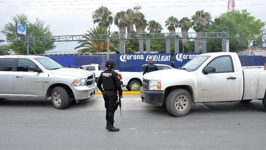 State police guard a beer distribution center after it was attacked in the town of Garcia, on the outskirts of the northern city of Monterrey, Mexico, Friday, June 19, 2015. A state government official said that the attackers invaded the property, demanded money from the workers and then started shooting, killing at least 10 people. The victims were all believed to be employees. (AP Photo/Emilio Vazquez)