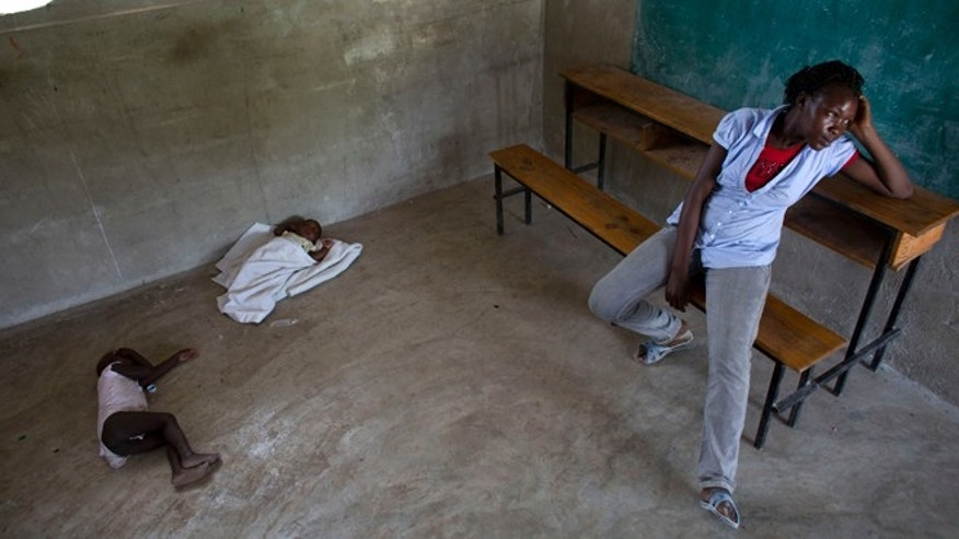 Milene Monime, 16, sits as her two-month-old son Jefferson Thezon, center, sleeps next to another person's child inside a school classroom where her family and others are staying after being deported the previous day from neighboring Dominican Republic, in the village of Fonbaya, Haiti, Thursday, June 18, 2015. People began preparing Thursday for deportation from the Dominican Republic after failing to obtain legal residency as part of a government program to crack down on migrants, most of them from neighboring Haiti or of Haitian descent. (AP Photo/Rebecca Blackwell)