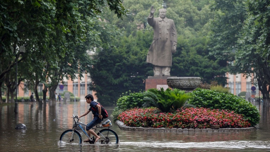 June 17, 2015: A bicyclist rides past a statue of late Chinese leader Mao Zedong on the flooded campus of Tongji University in Shanghai.