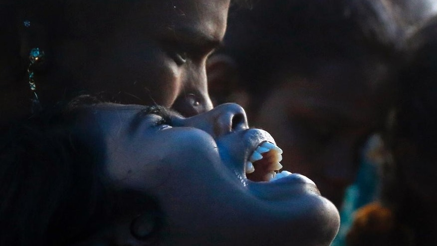 An Indian woman cries over the death of her family member who died after drinking tainted liquor at his funeral in Mumbai, India, Saturday, June 20, 2015. The death toll from drinking tainted liquor in a Mumbai slum climbed to more than 80 in the worst incident of its kind in more than a decade, police said Saturday.(AP Photo/Rajanish Kakade)
