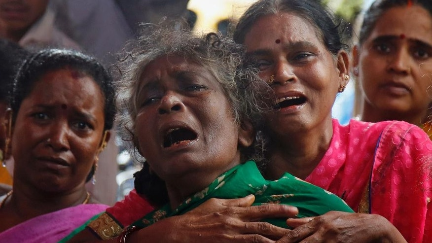 Family members of  Raja Ludraswami Harjan, who died after drinking tainted liquor, cry at his funeral in Mumbai, India, Saturday, June 20, 2015. The death toll from drinking tainted liquor in a Mumbai slum climbed to more than 80 in the worst incident of its kind in more than a decade, police said Saturday.(AP Photo/Rajanish Kakade)