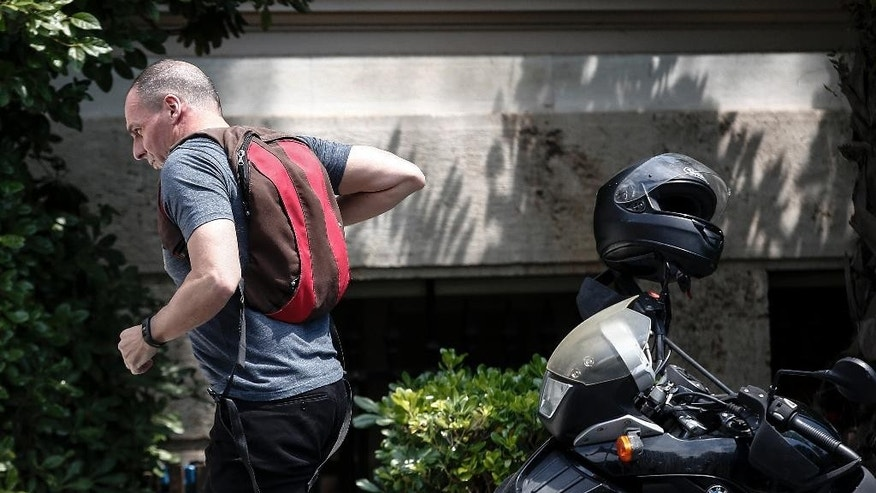Greece's Finance Minister Yanis Varoufakis leaves his motorcycle to enter a cabinet meeting at Greek Prime Minister's office in Athens, Greece, on Saturday, June 20, 2015. Greece is struggling to reach a deal with its creditors for new loans that it needs to avoid defaulting on debt payments at the end of the month. Without the bailout, Greece could be headed for bankruptcy or an exit from the 19-nation eurozone.  (AP Photo/Yorgos Karahalis)