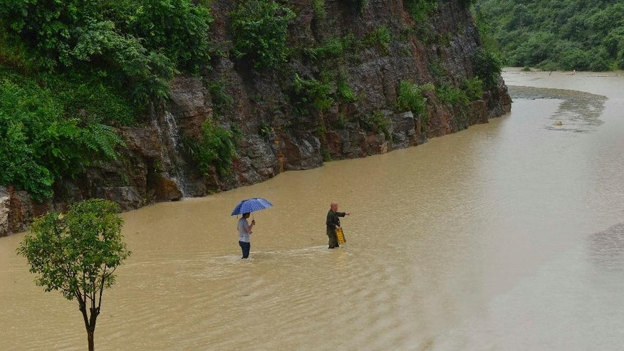 In this Thursday, June 18, 2015 photo, two men walk across a flooded stretch of roadway in Kaili city in southwestern China's Guizhou province.  Heavy storms have dumped more than 20 centimeters (nearly 8 inches) of rainfall in 48 hours on some towns, toppled thousands of homes, and dislocated tens of thousands of residents in several southern Chinese provinces, the the Ministry of Civil Affairs said Friday, June 19. (Chinatopix via AP) CHINA OUT