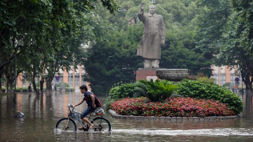 In this Wednesday, June 17, 2015 photo, a bicyclist rides past a statue of late Chinese leader Mao Zedong on the flooded campus of Tongji University in Shanghai. Heavy storms have dumped more than 20 centimeters (nearly 8 inches) of rainfall in 48 hours on some towns, toppled thousands of homes, and dislocated tens of thousands of residents in several southern Chinese provinces, the Ministry of Civil Affairs said Friday, June 19. (Chinatopix via AP) CHINA OUT