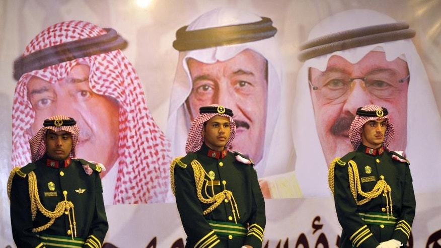 FILE - In this Feb. 18, 2014 file photo, Saudi royal guards stand on duty in front of portraits of King Abdullah bin Abdulaziz, right, then Crown Prince Salman bin Abdulaziz, center, and Muqrin bin Abdulaziz during a culture festival in Riyadh, Saudi Arabia. WikiLeaks is in the process of publishing more than 500,000 Saudi diplomatic documents to the Internet, the transparency website said Friday, June 19, 2015. If genuine, the documents would offer a rare glimpse into the inner workings of the notoriously opaque kingdom. (Fayez Nureldine/Pool Photo via AP, File)