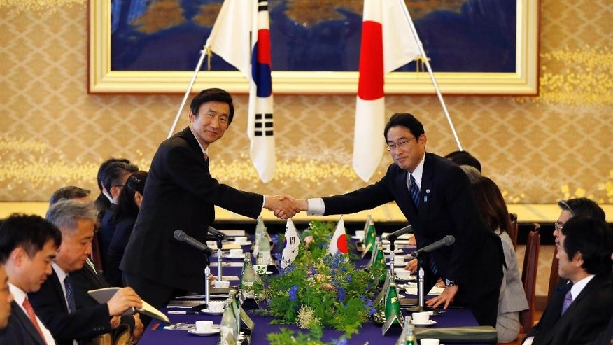 South Korea's Foreign Minister Yun Byung-se, left, shakes hands with Japan's Foreign Minister Fumio Kishida before their meeting at the foreign ministry's Iikura guest house in Tokyo Sunday, June 21, 2015. (Issei Kato/Pool Photo via AP)