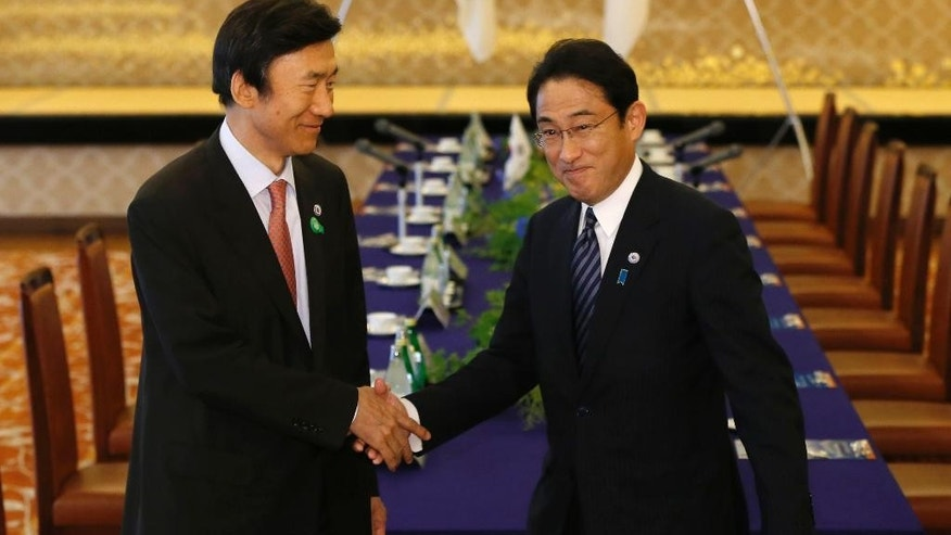 South Korea's Foreign Minister Yun Byung-se, left, shakes hands with Japan's Foreign Minister Fumio Kishida at the foreign ministry's Iikura guest house in Tokyo Sunday, June 21, 2015.  (Issei Kato/Pool Photo via AP)