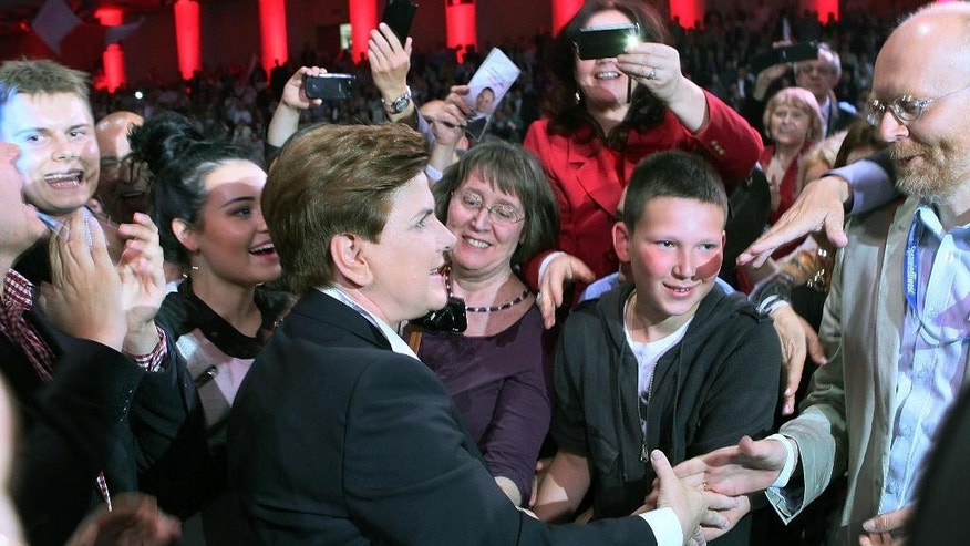 Opposition party's candidate for prime minister, Beata Szydlo, shakes hands with party members at the Law and Justice electoral convention in Warsaw, Poland, on Saturday, June 20, 2015. She is deputy head of the conservative Law and Justice party and heads its electoral campaign for the fall general elections. (AP Photo/Czarek Sokolowski)