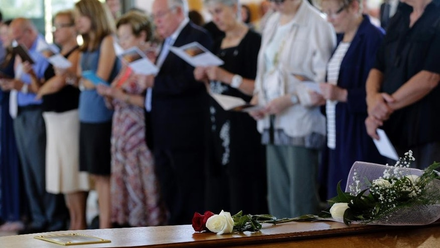 Flowers on top of a coffin with the remains of Robert Oliver Calvo, on a business trip when the Germanwings jet he was in crashed in the French Alps, during a religious funeral service in Montcada, near Barcelona, Spain, Saturday, June 20, 2015. Three months after the Germanwings jet crashed in the French Alps, hundreds of teary-eyed mourners have packed a funeral home to say goodbye. (AP Photo/Emilio Morenatti)