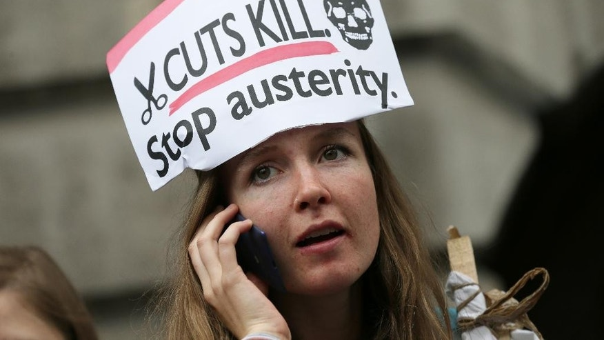 A demonstrator uses her phone outside the Bank of England during a protest against the Conservative Government and it's austerity policies in London, Saturday, June 20, 2015. The protest is intended to be peaceful, but demonstrators are angry at public sector cuts meant to address government deficits, which ballooned after Britain rescued troubled banks during the 2008 financial crisis. (AP Photo/Tim Ireland)