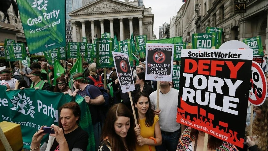 Demonstrators gather outside the Bank of England during a protest against the Conservative Government and it's austerity policies in London, Saturday, June 20, 2015. The protest is intended to be peaceful, but demonstrators are angry at public sector cuts meant to address government deficits, which ballooned after Britain rescued troubled banks during the 2008 financial crisis. (AP Photo/Tim Ireland)