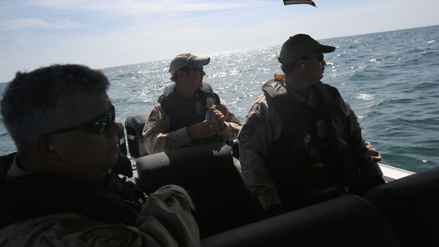 PORT ISABEL, TX - APRIL 12:  A boat crew from the U.S. Office of Air and Marine (OAM) looks towards a suspicious boat just across the Mexican border in the Gulf of Mexico on April 12, 2013 near Port Isabel, Texas. The crew patrols coastline waters near the U.S.-Mexico border searching for drug smugglers as well as illegal immigrants, which come across from Mexico near the mouth of the Rio Grande River. The Midnight Express interceptor is a 39 foot 900 horsepower craft capable of chasing smugglers down at 55 knots (63 mph). OAM units also push back illegal fishing boats out of U.S. waters.  (Photo by John Moore/Getty Images)
