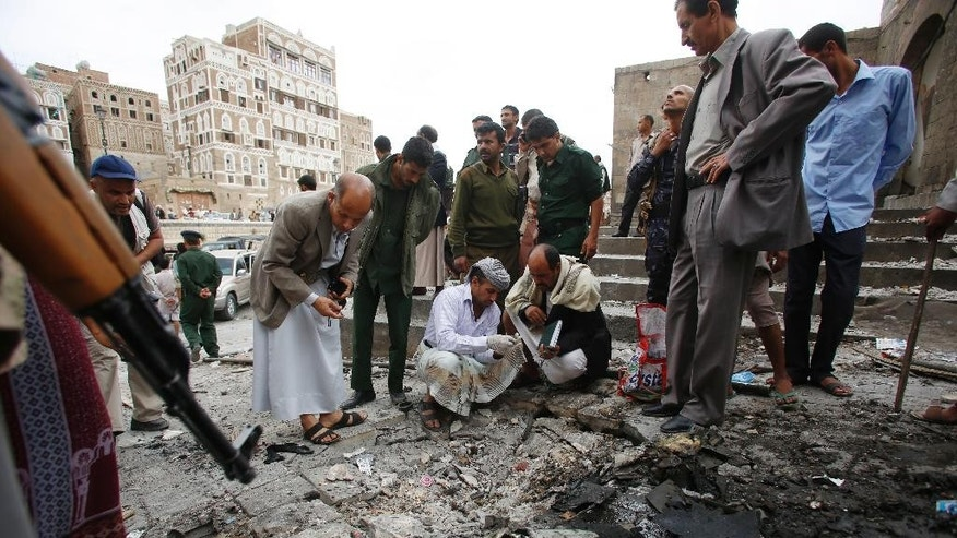 Yemenis inspect the site of an explosion near the old city of Sanaa, Yemen, Saturday, June 20, 2015. The car bomb exploded in front of a mosque in the capital Sanaa Saturday afternoon, killing several people and wounding at least six others, security officials said. The Islamic State branch in Yemen's capital claimed responsibility for the attack in a statement posted on an Islamic State twitter account, saying they were targeting Shiite Houthi rebels. (AP Photo/Hani Mohammed)