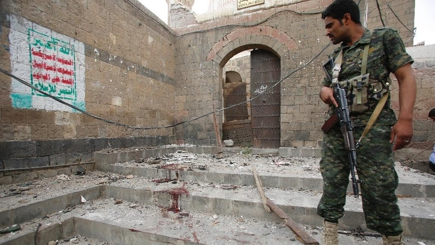 A Shiite Houthi rebel, wearing an army uniform stands guard at the site of an explosion near the old city of Sanaa, Yemen, Saturday, June 20, 2015. The car bomb exploded in front of a mosque in the capital Sanaa Saturday afternoon, killing several people and wounding at least six others, security officials said. The Islamic State branch in Yemen's capital claimed responsibility for the attack in a statement posted on an Islamic State twitter account, saying they were targeting Shiite Houthi rebels. (AP Photo/Hani Mohammed)