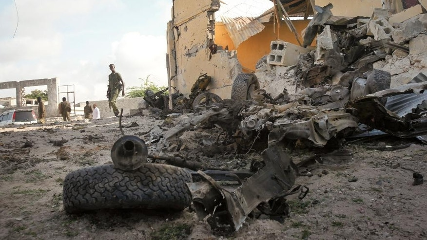 A Somali soldier observes the scene of a car bomb attack in the capital Mogadishu, Somalia Sunday, June 21, 2015. The al-Qaida-linked al-Shabab extremist group tried to attack a training compound used for intelligence officials in Mogadishu, a police officer said. (AP Photo)