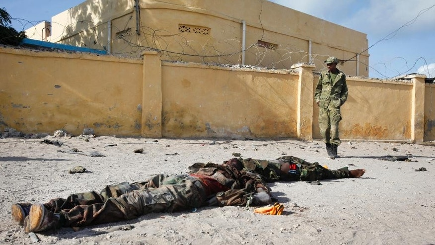 A Somali soldier walks past the bodies of two suspected al-Shabab fighters who were killed while engaging in a car bomb attack in the capital Mogadishu, Somalia Sunday, June 21, 2015. The al-Qaida-linked al-Shabab extremist group tried to attack a training compound used for intelligence officials in Mogadishu, a police officer said. (AP Photo)