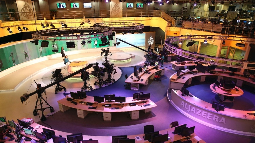 Jan. 1, 2015: Staff members of Al-Jazeera International work at the news studio in Doha, Qatar.