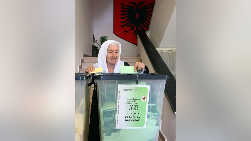 An Albanian  woman casts his ballot for the local municipal elections, in Tirana, Albania, Sunday, June 21, 2015. Albanians have started voting in local municipal elections, a key step in their efforts to launch membership negotiations with the European Union. Last year, Albania was granted EU candidate status and now Tirana is expecting to get approval for the launch of full membership negotiations.  (AP Photo/Hektor Pustina)