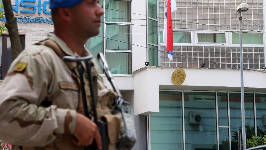 An Albanian soldier stands guard in Tirana, as the Albanian army are protecting embassies and other public institutions in the capital while some 6,000 police officers stay near the polling stations, as people cast their ballots for the local municipal elections, a key step in the country's  efforts to launch membership negotiations with the European Union, Tirana, Sunday, June 21, 2015. Some 3.4 million eligible voters cast their ballots in the country's seventh local polls since the fall of communism in 1990 to elect 61 mayors and 1,595 municipal counsellors.  (AP Photo/Hektor Pustina)