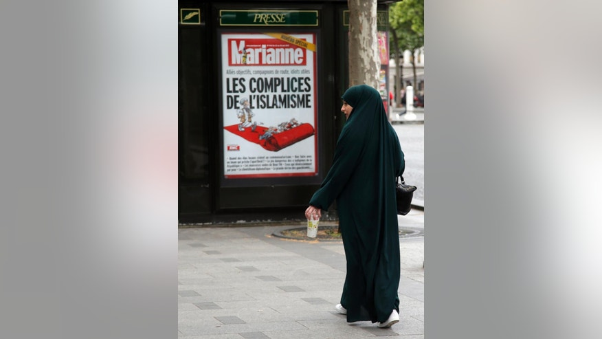"In this Thursday, May 21, 2015 photo a Muslim woman walks by a poster for French magazine Marianne reading ""Radical Islam Accomplice"", on the Champs Elysees in Paris. Its imams preach austere piety, its tenets demand strict separation of sexes _ and some of its most radical adherents are heeding the call of jihad. Salafism, an Islamic movement based on a literal reading of the Quran, is on the rise in France, Germany and Britain, security officials say, with Salafis sharply increasing their influence in mosques and on the streets. (AP Photo/Francois Mori)"