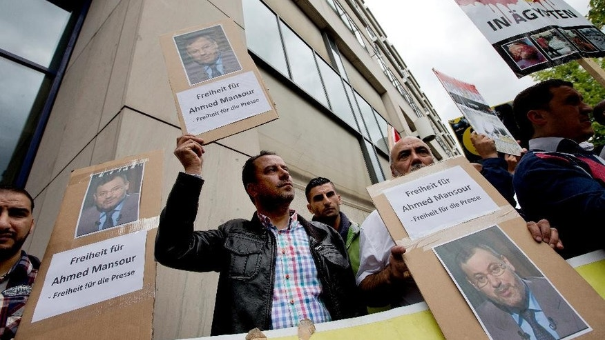 "Men hold protest posters in front of a court to support the release of the journalist Ahmed Mansour in Berlin, Germany, Sunday, June 21, 2015. Mansour, 52, a senior journalist with the Qatar-based broadcaster Al-Jazeera, was detained at Tegel airport on Saturday on an Egyptian arrest warrant, Al-Jazeera said. Posters read: ""Freedom for Ahmed Mansour - Freedom for the press"". (AP Photo/Michael Sohn)"