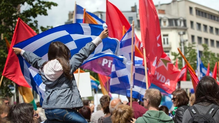 A girl sits on her father's shoulders as she unfurls the Greek flag during a protest march in solidarity with Greece in the center of Brussels on Sunday, June 21, 2015. Heads of state in the eurogroup will meet in Brussels on Monday for a special summit to discuss the financial crisis with Greece. (AP Photo/Virginia Mayo)