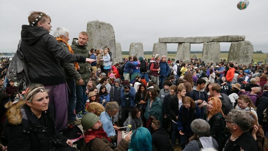 People stand on the stones as thousands of revellers gather at the ancient stone circle Stonehenge to celebrate the Summer Solstice, the longest day of the year, near Salisbury, England,Sunday, June 21, 2015. (AP Photo/Tim Ireland)