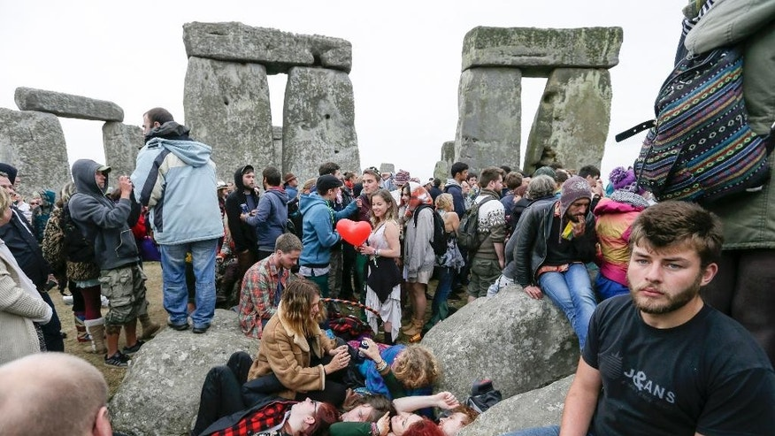 People lie down together as thousands of revellers gathered at the ancient stone circle Stonehenge to celebrate the Summer Solstice, the longest day of the year, near Salisbury, England, Sunday, June 21, 2015. (AP Photo/Tim Ireland)