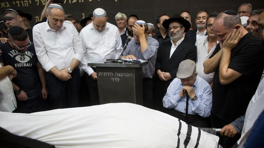 "Friends and relatives of Danny Gonen mourn next to his body during his funeral, at the cemetery in the city of Lod, near Tel Aviv, Israel, Saturday, June 20, 2015. Gonen was killed when a gunman opened fire at a car outside a West Bank settlement on Friday, killing an Israeli man and wounding another in what police said was a ""terror attack."" The Palestinian militant group Hamas praised the attack but stopped short of claiming responsibility. (AP Photo/Oded Balilty)"