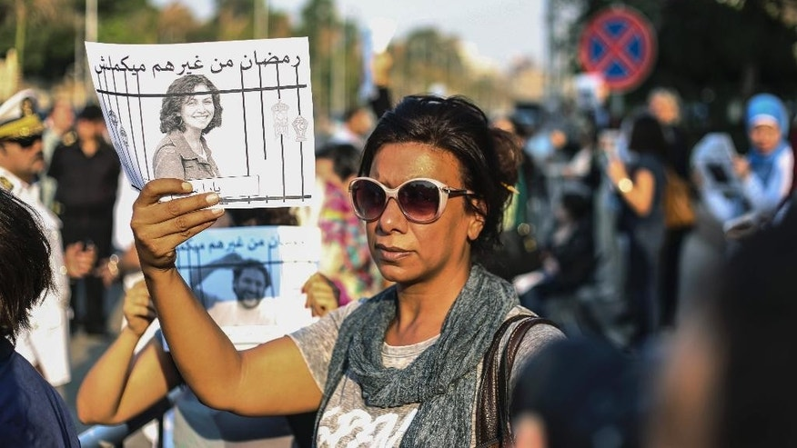 Egyptian women raise posters with people detained for violating the country's protest law as they hold a rally in front of a presidential palace in Cairo, Egypt, Sunday, June 21, 2015. The vigil Sunday outside the palace of President Abdel-Fatah el-Sissi didn't seek prior permission but ended peacefully. It comes a year after 23 secular activists, including a prominent rights defender, were arrested there for protesting against the law. (AP Photo/Mohamed el Raai)