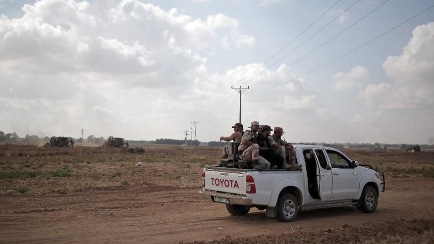 June 10, 2015: In this photo, Palestinian Hamas gunmen ride on the back of a pick-up truck as they patrol the border with Israel near the southern Gaza Strip town of Khan Younis, as Israeli military bulldozers are seen in the background.