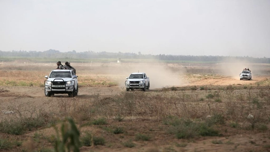 June 10, 2015: In this photo, Palestinian Hamas gunmen ride on the back of a pick-up truck as they patrol the border with Israel near the southern Gaza Strip town of Khan Younis.
