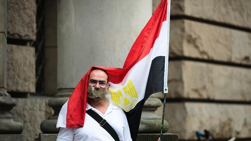 A man with tape on his mouth and an Egyptian  flag attends a demonstration in front of a court to  demand the release of the journalist Ahmed Mansour in Berlin, Germany, Monday, June 22, 2015.  Ahmed Mansour, 52, a senior journalist with the Qatar-based broadcaster Al-Jazeera, was detained at Tegel airport on Saturday on an Egyptian arrest warrant, Al-Jazeera said. (AP Photo/Markus Schreiber)