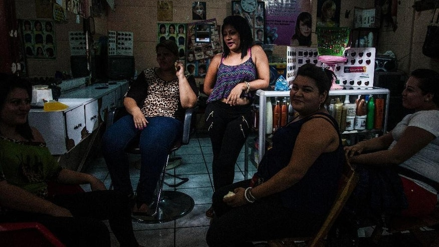 In this June 12, 2015 photo, hairdressers take a break from their work at a hair salon in downtown San Salvador, El Salvador. Violence in El Salvador is reaching a level that rivals the worst days of guerrilla warfare decades ago, few are willing to risk becoming a target. Word on the street is that only the girlfriends of gang members are allowed to be redheads or blondes. So in this violent place, women are scurrying to salons to give up their blond hair and highlights, to dye it all black, not out of fashion sense, but out of fear. (AP Photo/Manu Brabo)