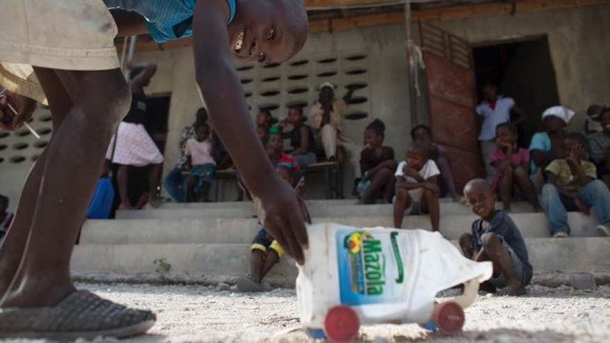 In this Thursday, June 18, 2015 photo, a youth who was recently deported from neighboring Dominican Republic with his family plays with a truck made from a vegetable oil bottle and bottle caps, outside a school building where residents have allowed the families to stay, in the village of Fonbaya, Haiti. Thousands of people began preparing Thursday for deportation from the Dominican Republic after failing to obtain legal residency as part of a government program to crack down on migrants, most of them from neighboring Haiti or of Haitian descent. (AP Photo/Rebecca Blackwell)