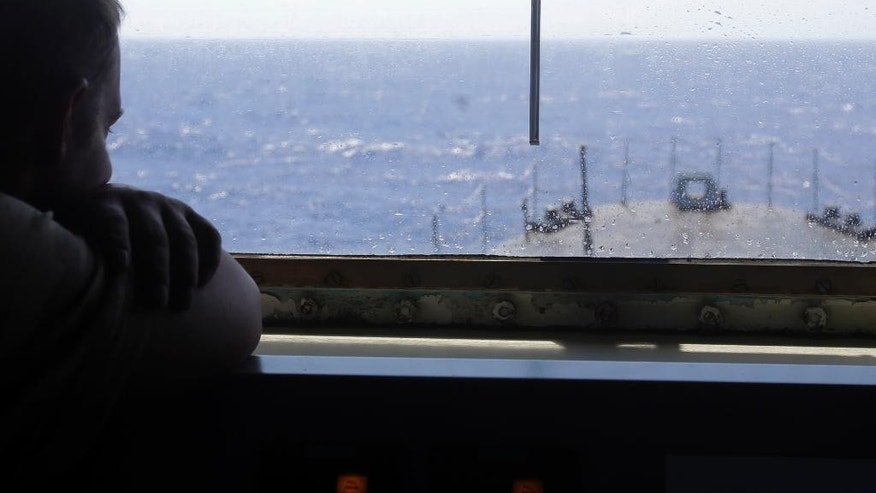 Sailor First Class Michael Christiaens looks the skyline through a glass window of the command deck of the Belgian Navy Vessel Godetia breaks during a migrants search and rescue mission in the mediterranean sea off the Sicilian coasts, Italy, Sunday, June 21, 2015. The Godetia Belgian Navy Vessel is among a EU Navy Vessels fleet taking part in the Triton migrant rescue operations. (AP Photo/Gregorio Borgia)
