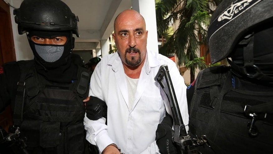 FILE - In this March 11, 2015 file photo, Serge Atlaoui, center, a French national who is on death row after being convicted of drug offences, is escorted by armed police officers upon arrival for his judicial review hearing at the district court in Tangerang, Indonesia. The administrative court on Monday, June 22, 2015 denied the final appeal of the French national facing execution for drug offenses. (AP Photo/Tatan Syuflana, File)