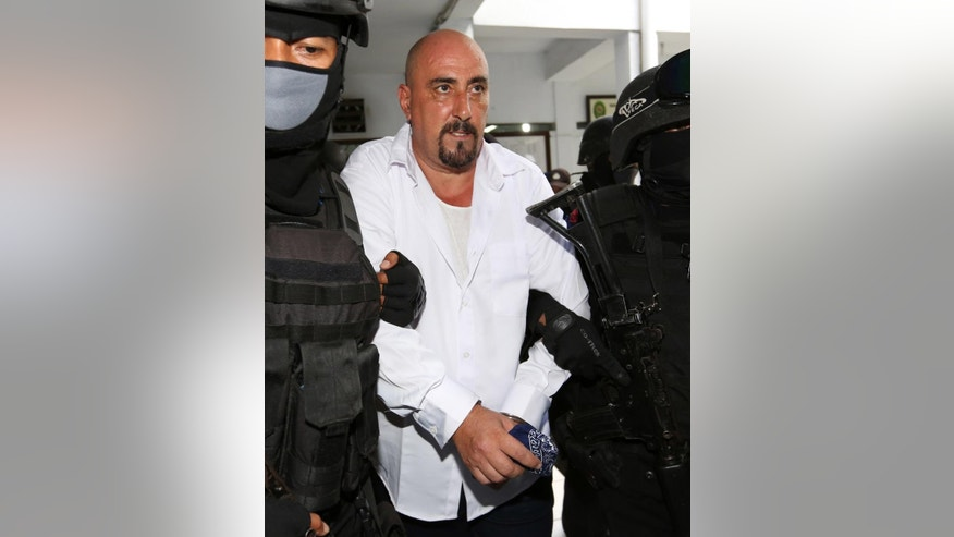 FILE - FILE - In this March 11, 2015 file photo, Serge Atlaoui, center, a French national who is on death row after being convicted of drug offences, is escorted by armed police officers upon arrival for his judicial review hearing at the district court in Tangerang, Indonesia. The administrative court on Monday, June 22, 2015 denied the final appeal of the French national facing execution for drug offenses. (AP Photo/Tatan Syuflana, File)