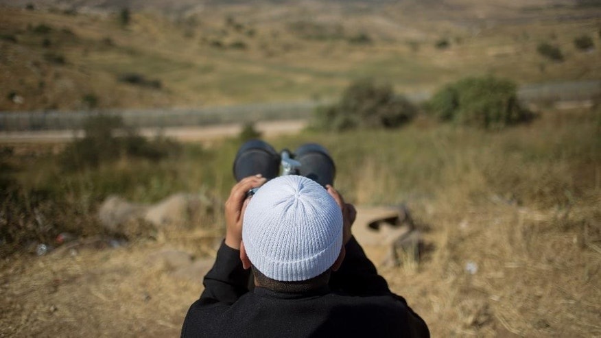 In this photo taken on Wednesday, June 17, 2015, a young member of the Druze minority watches the fighting between forces loyal to Syrian President Bashar Assad and rebels in the Druze village of Khader in Syria, from the Israeli-controlled Golan Heights. Members of Israel's Druze minority are concerned about their brethren in Syria. Now, they are asking Israel to help the Druze in Syria, even offering to go fight there if needed. (AP Photo/Ariel Schalit)