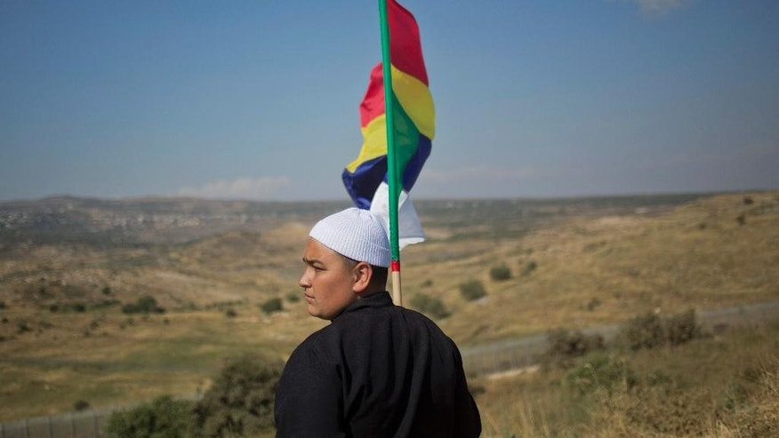 In this photo taken on Wednesday, June 17, 2015, a young member of the Druze minority waves the Druze flag as he watches the fighting between forces loyal to Syrian President Bashar Assad and rebels in Druze village of Khader in Syria, from the Israeli-controlled Golan Heights. The Israeli government insists it will not allow the Druze to be massacred but has otherwise kept quiet, looking to maintain the low profile it has kept since the uprising against Assad began in March 2011. (AP Photo/Ariel Schalit)