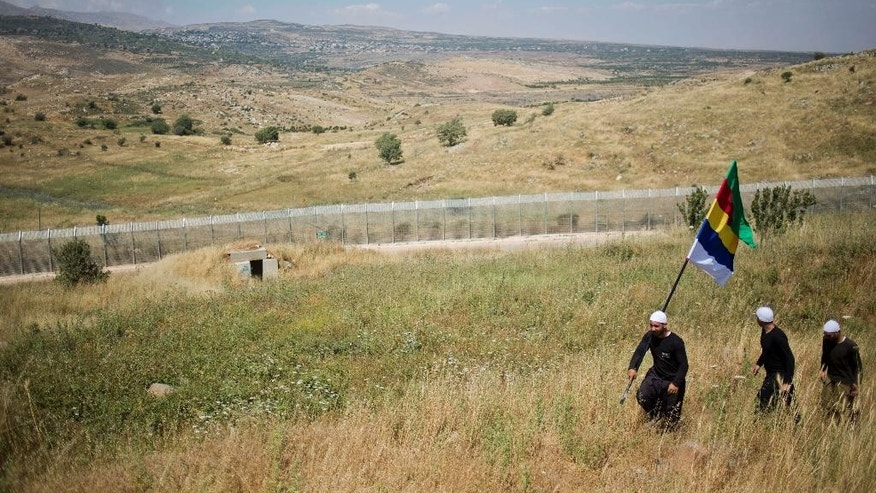 In this photo taken on Tuesday, June 16, 2015, a member of the Druze minority carries the Druze flag as they walk near the border with Syria in Israeli-controlled Golan Heights, while the fighting between forces loyal to Syrian President Bashar Assad and rebels in Druze village of Khader in Syria continues. Members of Israel's Druze minority are concerned about their brethren in Syria. Now, they are asking Israel to help the Druze in Syria, even offering to go fight there if needed. (AP Photo/Ariel Schalit)