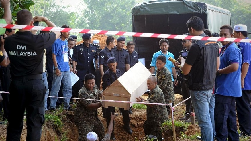 Malaysian police carries a coffin containing the remains of a Rohingya migrant for a mass burial ceremony in Kedah, Malaysia Monday, June 22, 2015. Malaysian authorities have given a Muslim burial to 21 human trafficking victims, believed to be Rohingya Muslim refugees, found in shallow graves in jungles bordering Thailand.  (AP Photo/Gary Chuah)