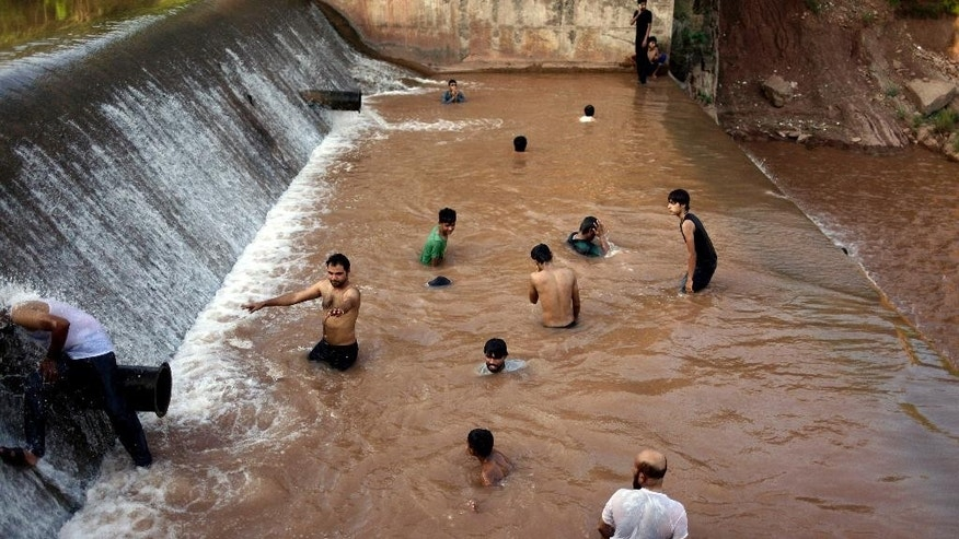 Pakistani youths cool off themselves at a river on the outskirts of Islamabad, Pakistan, Sunday, June 21, 2015. Many cities in Pakistan are facing heat wave conditions with temperatures reaching 49 degrees Celsius (120.2 Fahrenheit). (AP Photo/Anjum Naveed)