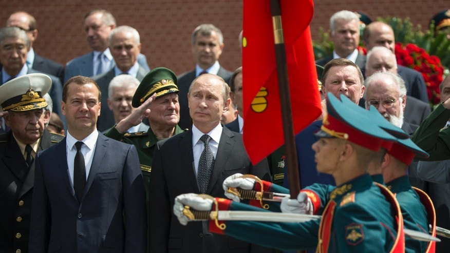June 22, 2015 - Russian President Vladimir Putin, center, and Russian Prime Minister Dmitry Medvedev, left, take part in a wreath laying ceremony at the Tomb of the Unknown Soldier in Moscow to mark the 74th anniversary of the Nazi invasion of the Soviet Union. The Kremlin said Putin spoke by phone Monday with French President Francois Hollande and German Chancellor Angela Merkel about the situation in eastern Ukraine.