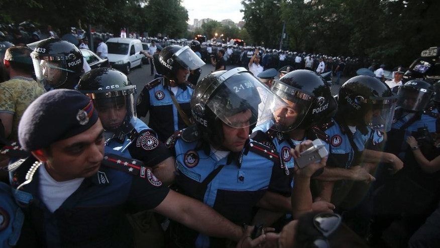 In this photo taken late Monday, June  22, 2015, Armenian riot police block demonstrators during a protest in the Armenian capital of Yerevan against a hike in electricity prices. Police in the Armenian capital have dispersed several hundred demonstrators who blocked a central avenue as part of their protest. About 5,000 demonstrators marched Monday to the presidential headquarters, but were stopped by phalanxes of riot police backed by water cannons. (Hrant Khachatryan/PAN Photo via AP)