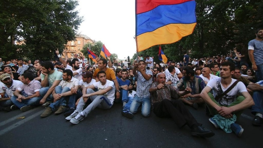 In this Monday, June  22, 2015 photo, demonstrators with Armenian national flags attend a protest in the Armenian capital of Yerevan against a hike in electricity prices. Police in the Armenian capital have dispersed several hundred demonstrators who blocked a central avenue as part of their protest. About 5,000 demonstrators marched Monday to the presidential headquarters, but were stopped by phalanxes of riot police backed by water cannons. (Hrant Khachatryan/PAN Photo via AP)